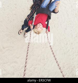 Elevated view of a woman pushing her son on a swing - Stock Photo