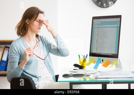 Woman at work suffering from headache. - Stock Photo