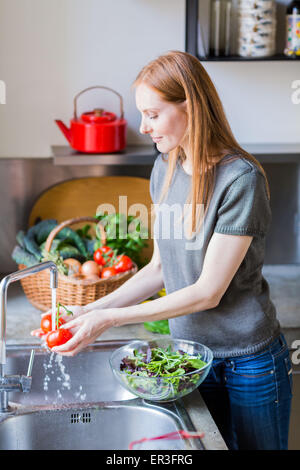 Woman washing vegetables. - Stock Photo