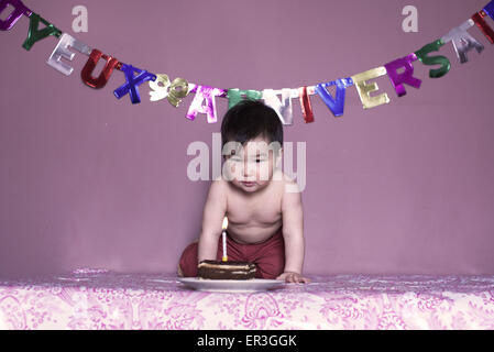 Baby blowing out birthday candle - Stock Photo