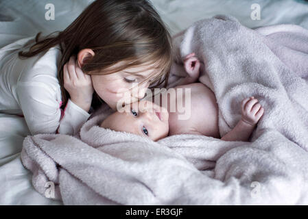 Little girl kissing baby brother's cheek on bed - Stock Photo