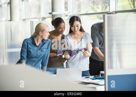 Colleagues looking through catalog together - Stock Photo