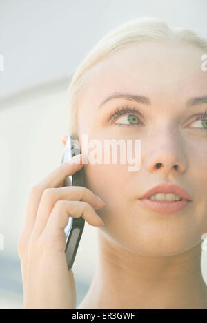 Woman talking on cell phone with serious expression on face - Stock Photo