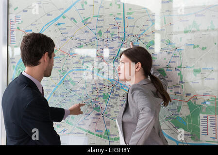 Man and woman planning route on Paris metro - Stock Photo