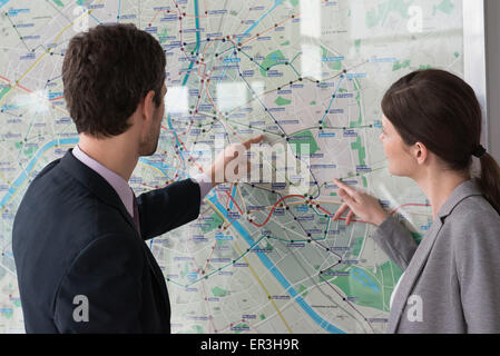 Man and woman looking at Paris metro map together - Stock Photo