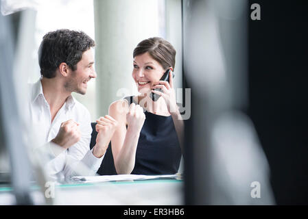 Business associates pleased by good news phone call - Stock Photo