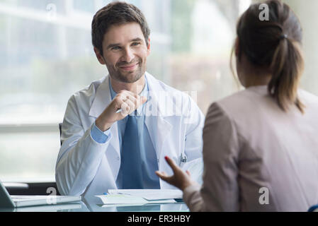 Doctor listening to patient express concerns during consultation - Stock Photo