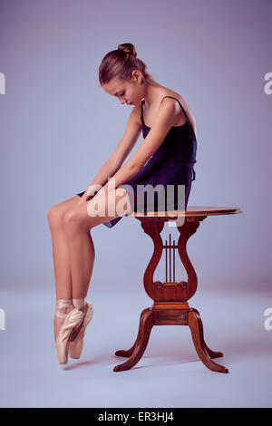 young ballerina sitting on wooden chair - Stock Photo