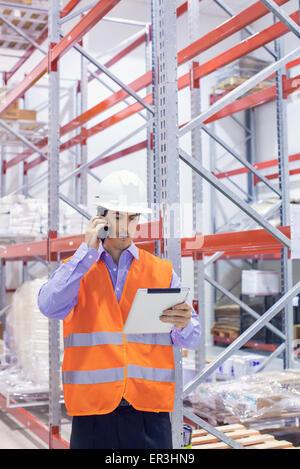 Engineer working in warehouse - Stock Photo