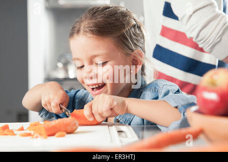 Little girl slicing carrots in kitchen - Stock Photo