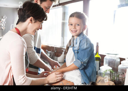 Family spending time together in kitchen, girl sitting on counter holding mother's hands - Stock Photo