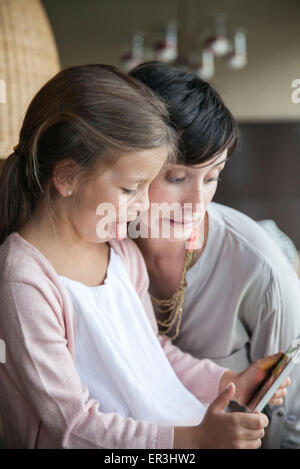 Mother and young daughter using digital tablet and making funny faces - Stock Photo