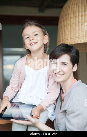 Mother and young daughter using digital tablet together - Stock Photo