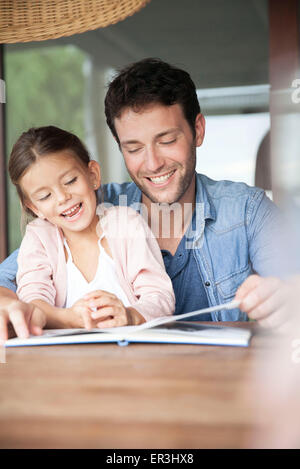 Father and daughter reading book together - Stock Photo