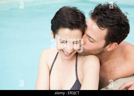 Couple relaxing in pool, man kissing woman's cheek - Stock Photo