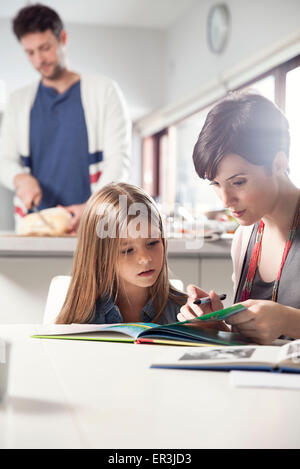 Mother and daughter reading book together - Stock Photo