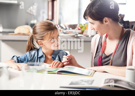 Mother and young daughter reading together - Stock Photo