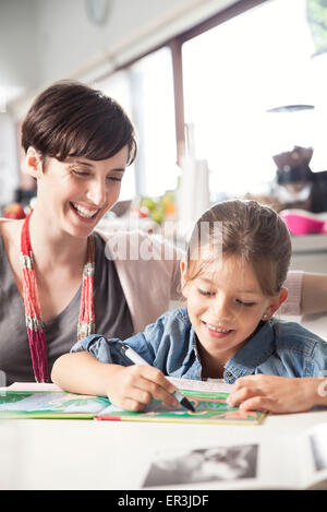 Mother teaching young daughter to read Stock Photo