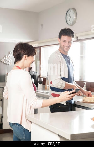 Couple looking at smartphone together while preparing food in kitchen - Stock Photo
