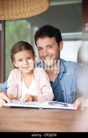 Father and daughter reading together, portrait - Stock Photo