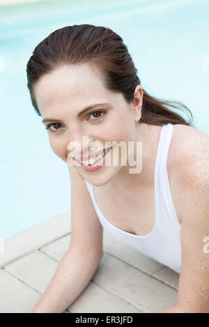 Young woman sunbathing by pool, smiling, portrait - Stock Photo