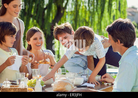 Family enjoying breakfast together outdoors - Stock Photo