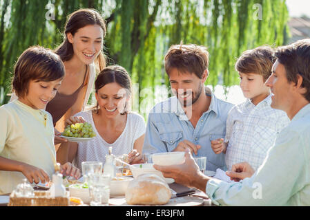 Family enjoying breakfast together outdoors - Stock Photo