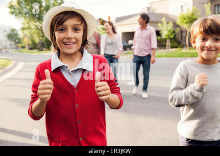 Boys playing outdoors, family in background - Stock Photo