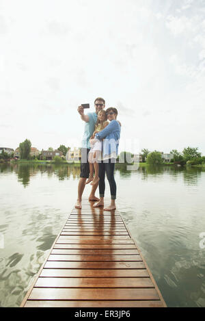 Family with young daughter standing together at end of lake pier taking selfie - Stock Photo
