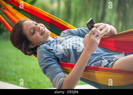 Woman relaxing in hammock with smartphone - Stock Photo