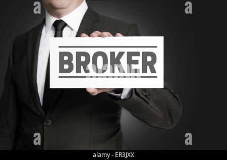 Broker sign is held by businessman. - Stock Photo