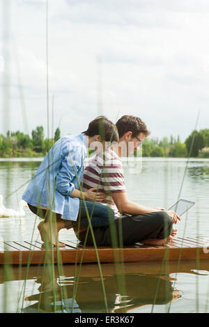 Couple using laptop computer on dock - Stock Photo
