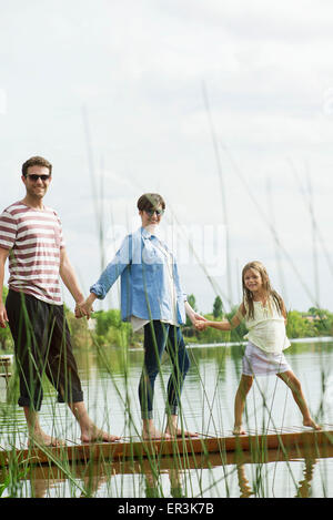 Family holding hands on dock, portrait - Stock Photo