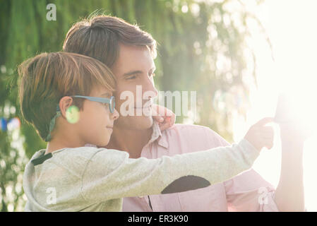 Father and son embracing outdoors, overexposure - Stock Photo