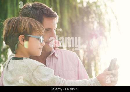 Father and son posing for photograph with smartphone, overexposure - Stock Photo