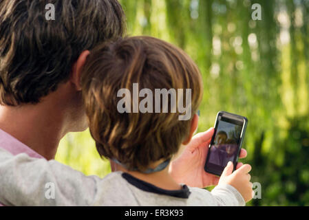 Father and son posing for photograph with smartphone - Stock Photo