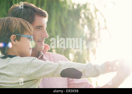 Father and son together outdoors, overexposure - Stock Photo