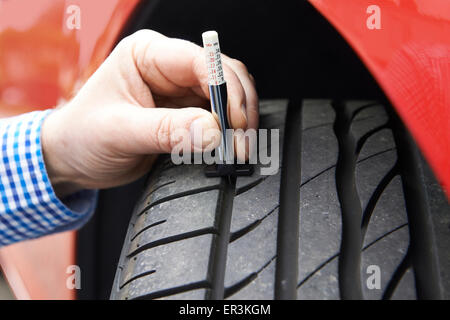 Close-Up Of Man Checking Tread On Car Tyre With Gauge - Stock Photo