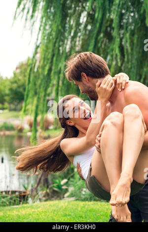 Young man playfully carrying girlriend - Stock Photo