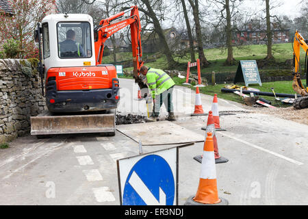 Two workmen digging a trench across a road with a mechanical digger - Stock Photo