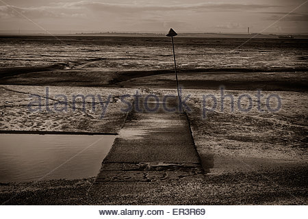 Black and white landscape image, jetty out in to an empty estuary, Leigh on Sea, Essex. The Kent coastline in the - Stock Photo
