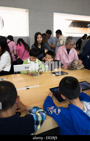 Chinese shoppers crowd the interior of the Apple store to see latest computer hardware phones and  watches in Shanghai - Stock Photo