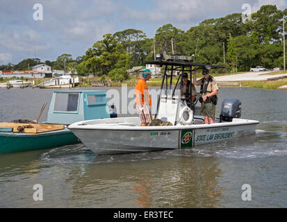 Eastpoint, Florida - Officers from the Florida Fish and Wildlife Commission talk to an oysterman on Apalachicola - Stock Photo