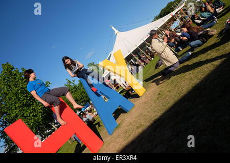 Hay Festival, Powys, Wales - May 2015  - Two young girls reading books on top of the giant HAY sign on the Festival - Stock Photo