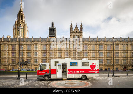 NHS mobile blood bank vehicle parked outside Westminster's Parliament buildings in London, UK. - Stock Photo