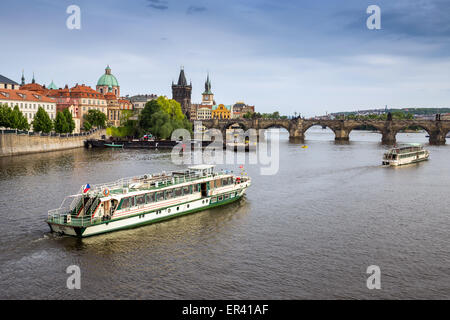 Sightseeing tour boat at Charles Bridge on river Vltava Prague city Czech Republic Europe - Stock Photo