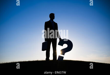 Businessman holding Question mark on the hill - Stock Photo