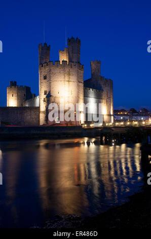 Caernarfon Castle at twilight dusk night from across Seiont estuary Gwynedd North Wales UK - Stock Photo