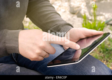Man holds the tablet in hand - Stock Photo