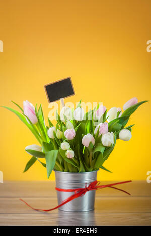 Tulips in a bucket against a yellow backdrop - Stock Photo